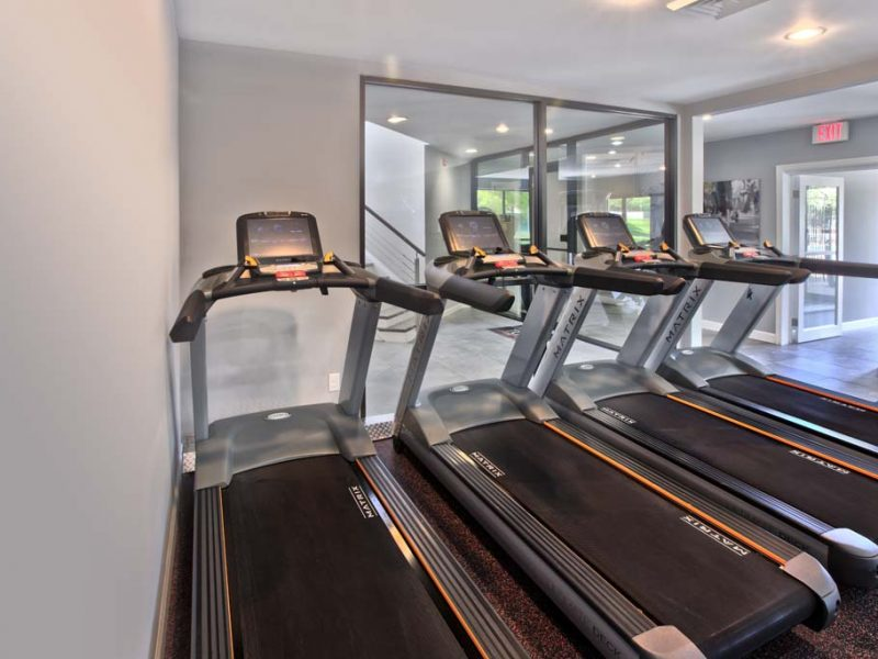 This image showcases the commercial fitness with State-of-the-art athletic club with equipment that is essential for community amenities and offering a high-quality cardio machine.